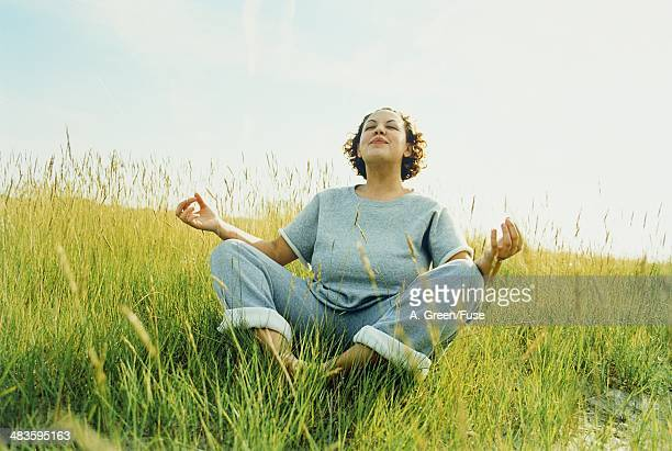 Young woman meditating on a meadow