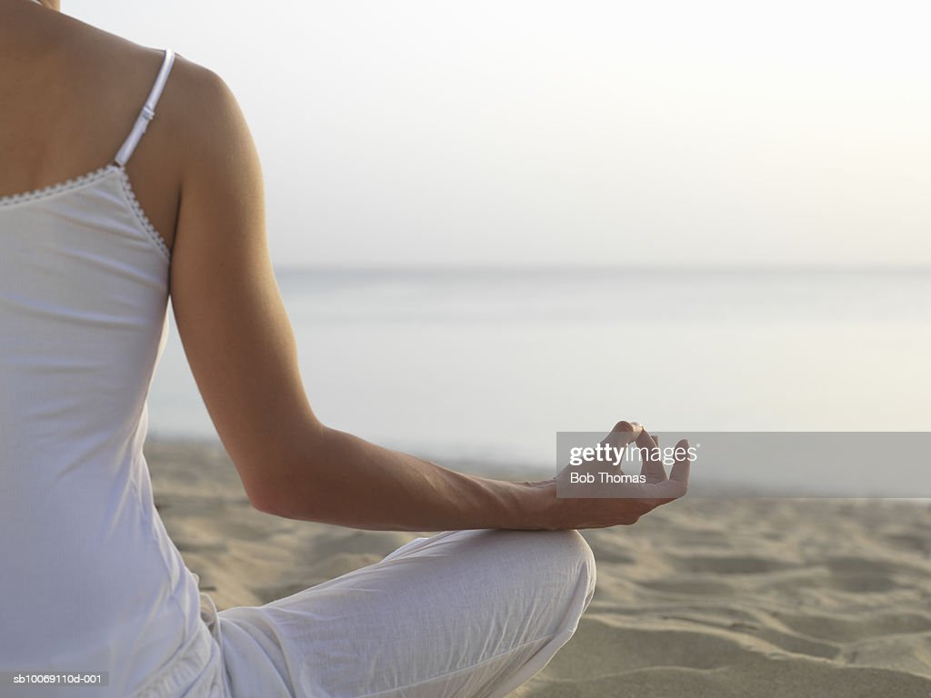 Young woman meditating on beach, rear view, mid section : Stockfoto