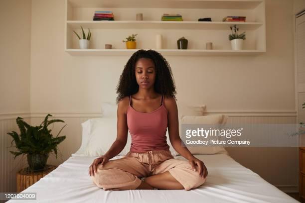 jovem meditando em sua cama de manhã - parte de uma série - fotografias e filmes do acervo