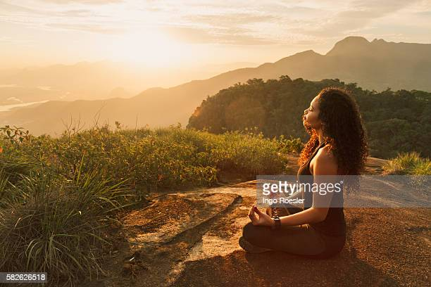 young woman meditating on mountain top - meditieren stock-fotos und bilder