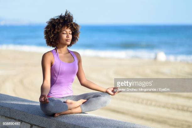 young woman meditating on retaining wall at beach - meditation imagens e fotografias de stock