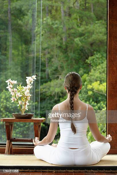Young woman meditating on tatami mat near window, rear view