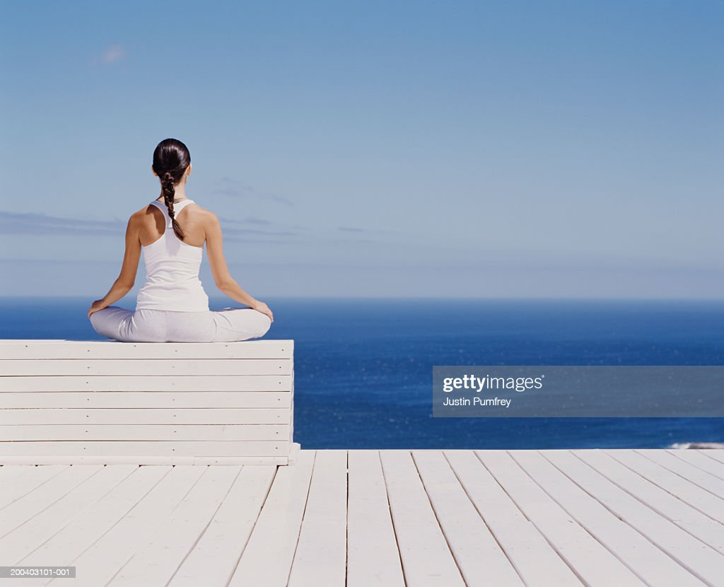 Young woman meditating on wooden block, rear view : Stock Photo