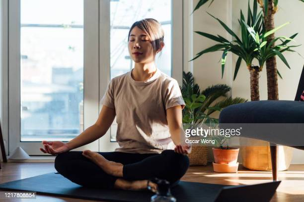 young woman meditating on yoga mat at home - relaxation stock pictures, royalty-free photos & images