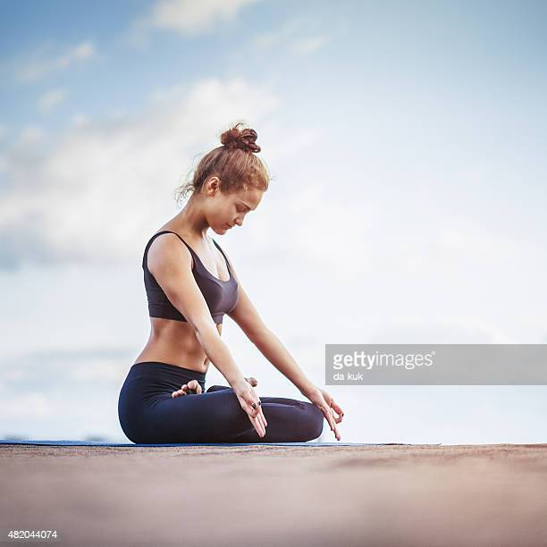 Young woman meditating outdoors on a rooftop
