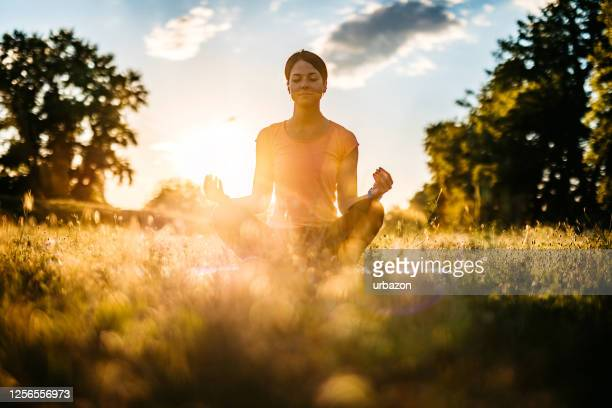 young woman meditating outdoors - hinduism stock pictures, royalty-free photos & images