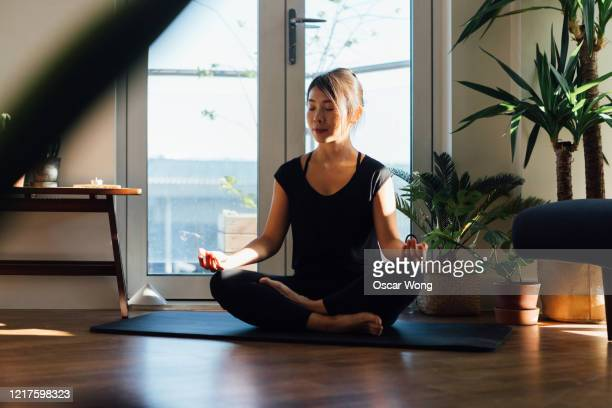 young woman meditating while sitting at home - flatten the curve stock pictures, royalty-free photos & images