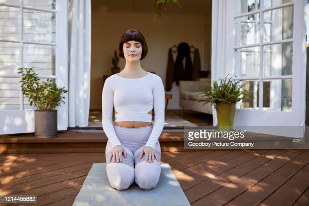 young woman meditating with her eyes closed on her patio - kneeling stock pictures, royalty-free photos & images