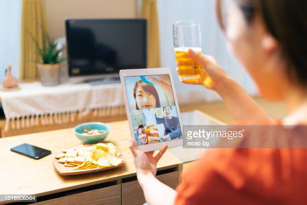 junge frau trifft ihre lieben per videokonferenz und trinkt gemeinsam bier - corona beer stock-fotos und bilder