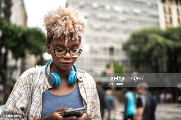 giovane donna che messaggi su smarthphone per strada - nativo digitale foto e immagini stock