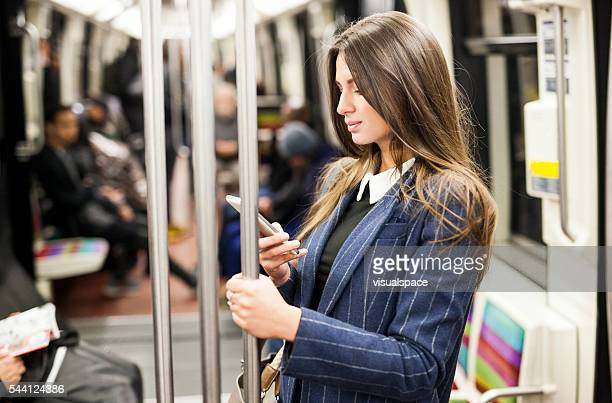 Young Woman Messaging Online While On Subway