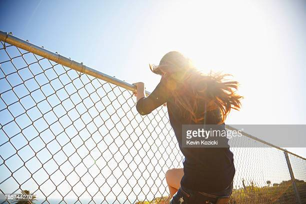 young woman messing about on wire fence - hek stockfoto's en -beelden