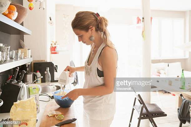 Young woman mixing dough at kitchen