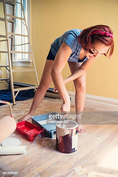 Young woman mixing paint getting ready to improve a room.
