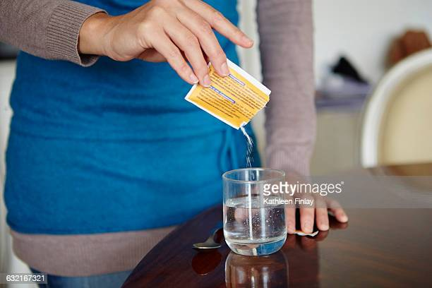 Young woman mixing water-soluble medication from sachet, in glass of water