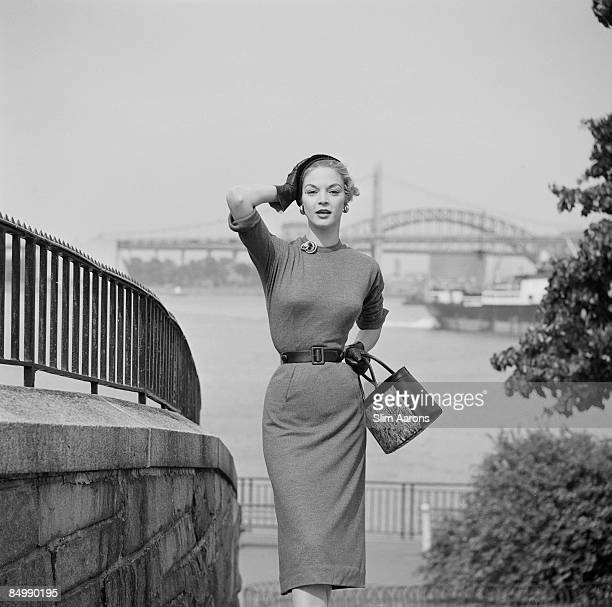 A young woman modelling a belted dress with pencil skirt New York City June 1953
