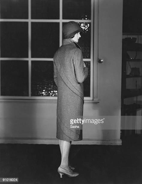 Young woman modelling a three-quarter length coat with spiral trim and a cloche hat, March 1929.