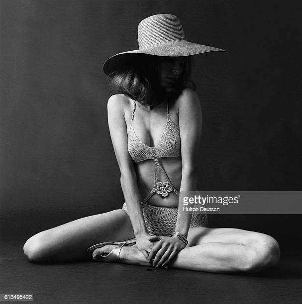 Young woman models a skimpy, knit-pattern, swimsuit, and straw sun hat.