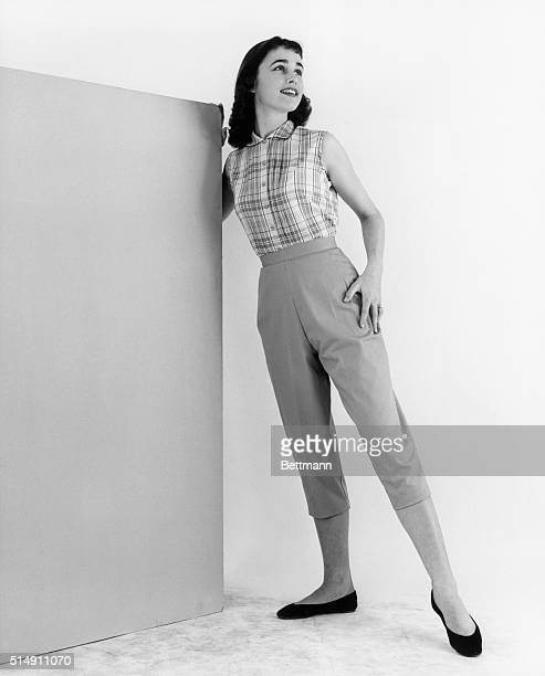 A Young woman models a sleeveless plaid blouse and capri pants with flat shoes