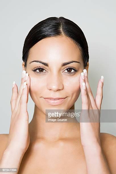 Young woman moisturizing