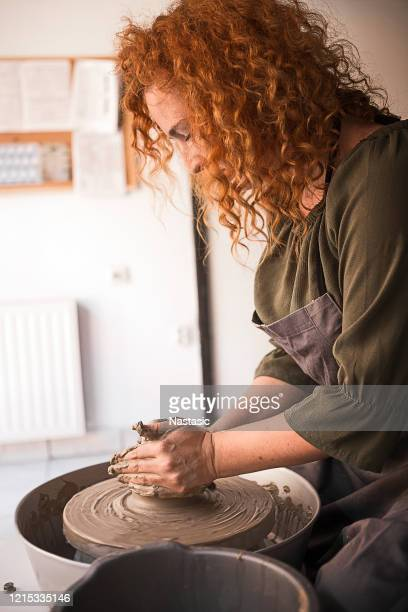 young woman molding clay on pottery wheel - turning stock pictures, royalty-free photos & images
