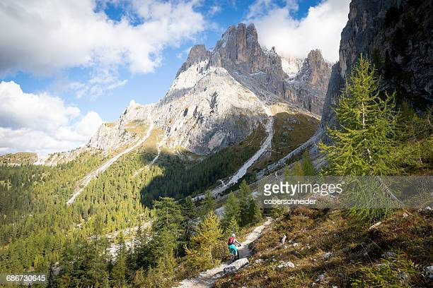 Young woman mountain biking in the Dolomites, Val gardena, South Tyrol, italy