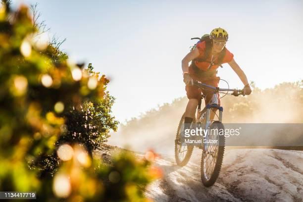 young woman mountain biking over rocks, monterey, california, usa - mountain bike stock pictures, royalty-free photos & images