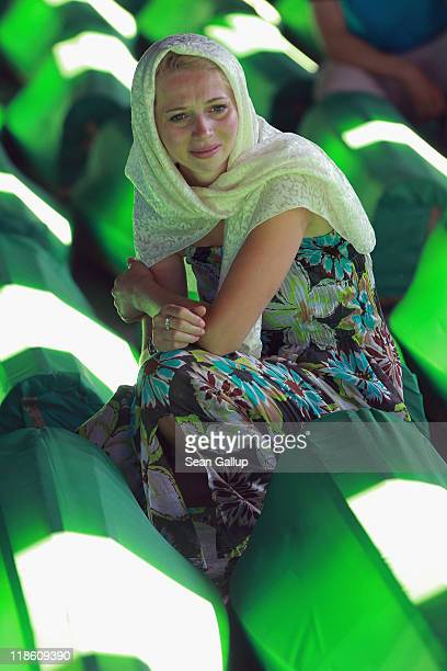 A young woman mourns over a coffin among 613 coffins of victims of the 1995 Srebrenica massacre in a hall at the Potocari cemetery and memorial near...