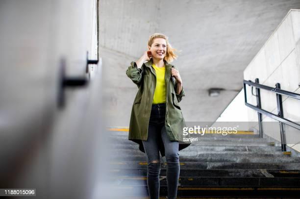 junge frau bewegt sich die treppe am bahnhof - unterirdisch stock-fotos und bilder