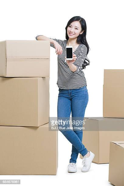 Young woman moving house and showing a smart phone