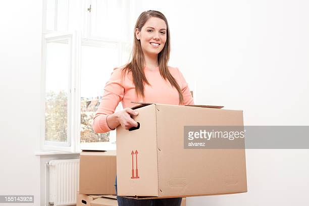 Young woman moving house having fun