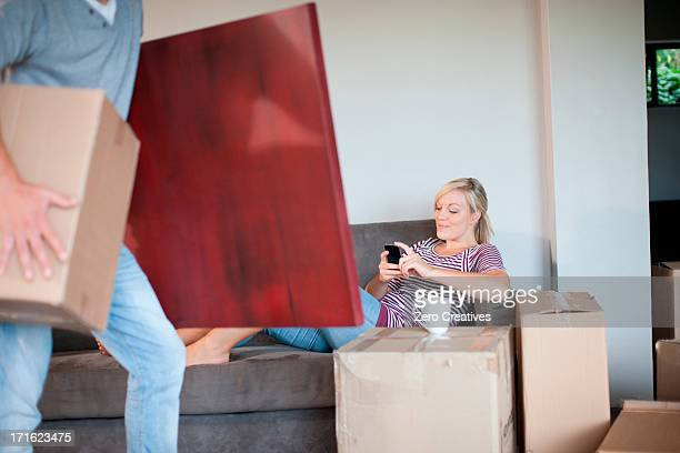Young woman moving house on sofa with cell phone
