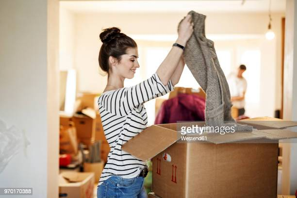 young woman moving house, unpacking cardboard boxes - unpacking stock pictures, royalty-free photos & images