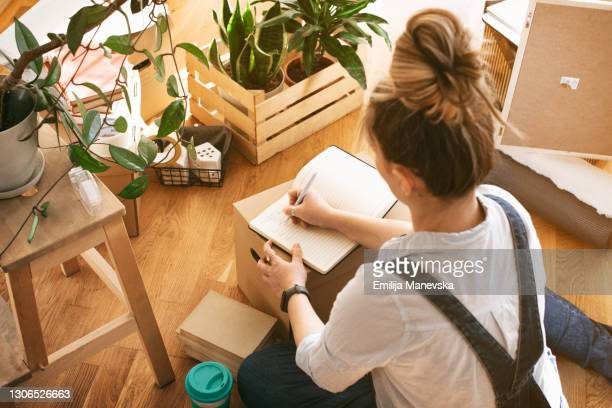 young woman moving in into new apartment - list stock pictures, royalty-free photos & images