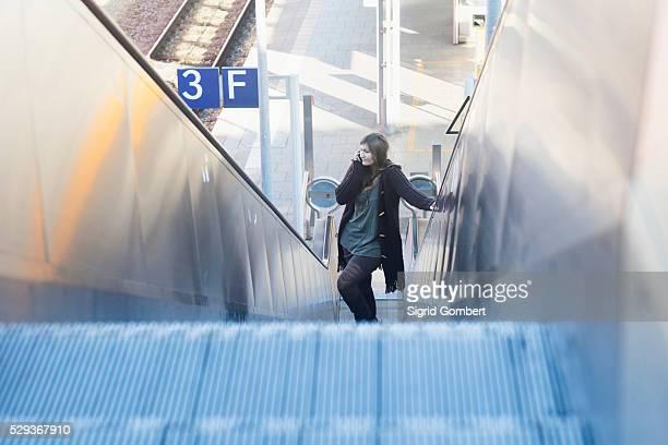 young woman moving on escalator and talking on phone at railway station, freiburg im breisgau, baden-w��rttemberg, germany - sigrid gombert fotografías e imágenes de stock