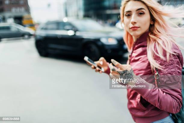 young woman moving through a city holding smartphone - leben in der stadt stock-fotos und bilder