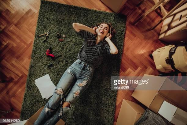 junge frau umzug in eine neue wohnung. anhören von musik auf einem teppich liegend - lying down stock-fotos und bilder