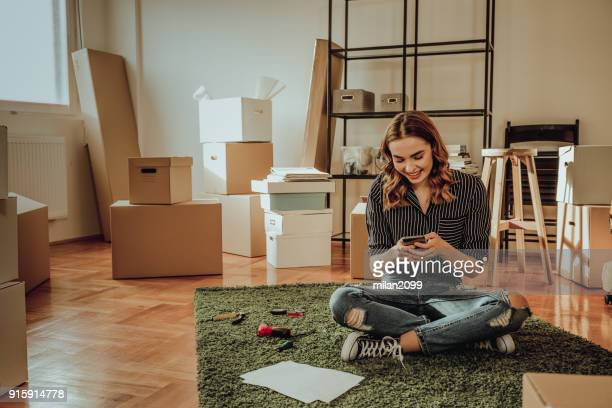 young woman moving to a new apartment. typing a message while sitting down on a carpet - unpacking stock pictures, royalty-free photos & images