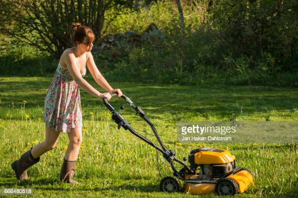 Young woman mowing the lawn