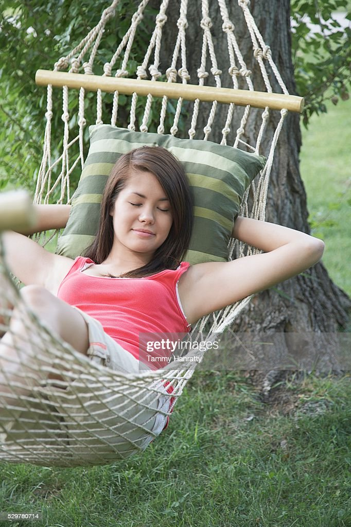 Young woman napping in hammock : Stock Photo