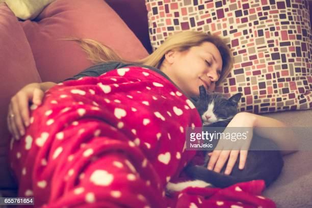 Young woman napping on the couch with her cat together