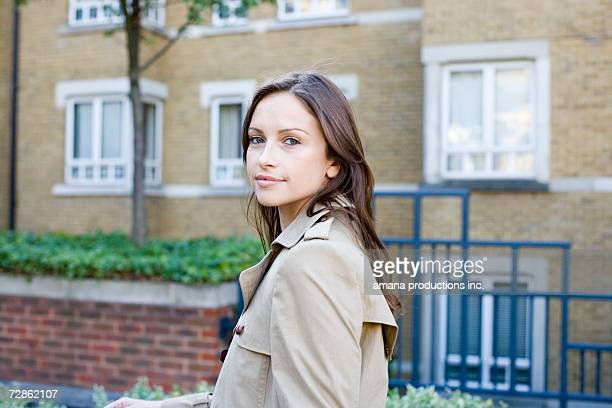 young woman near apartment building - トレンチコート ストックフォトと画像