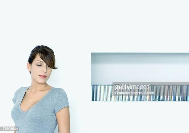 young woman next to shelf of cds - à côté de photos et images de collection