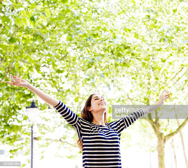 Young woman next to trees with arms in the air