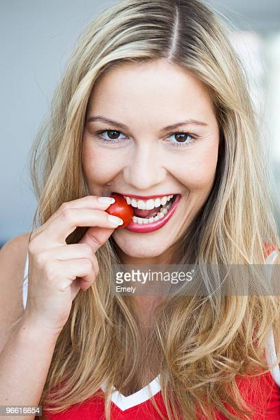 Young woman nibbling on tomato