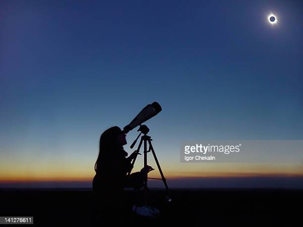 Young woman observing total solar eclipse