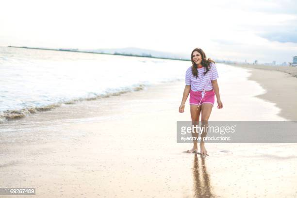 young woman of hispanic ethnicity playing in the waves on Seal Beach in California on the edge of the ocean near the waves and water