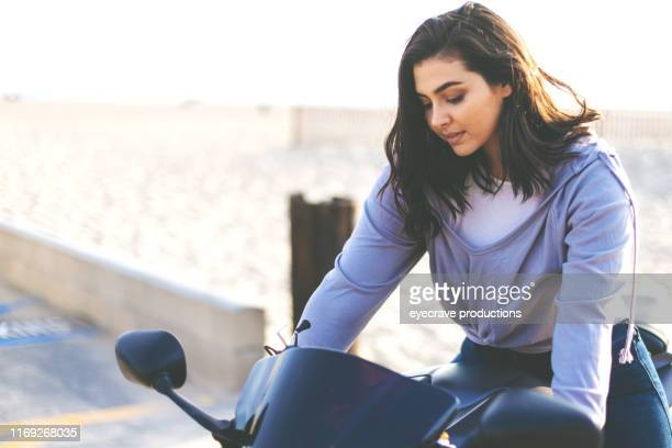 Young woman of Lebanese Ethnicity on motorcycle in parking lot of Seal Beach in California