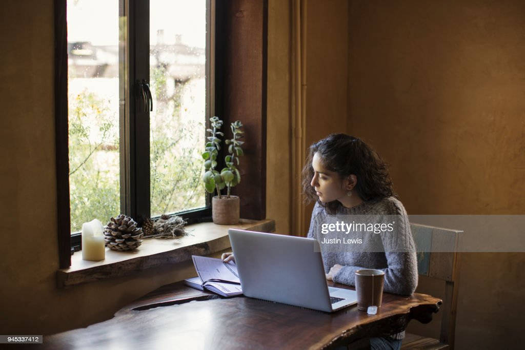 Young Woman of Mixed-ethnicity Works From Home Using Laptop Computer and Reference Book : Stock Photo