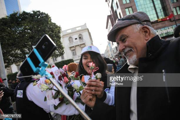 A young woman offers roses to an elderly man during the celebrations of the Revolution Day the heightyear anniversary of the overthrow of the 23year...